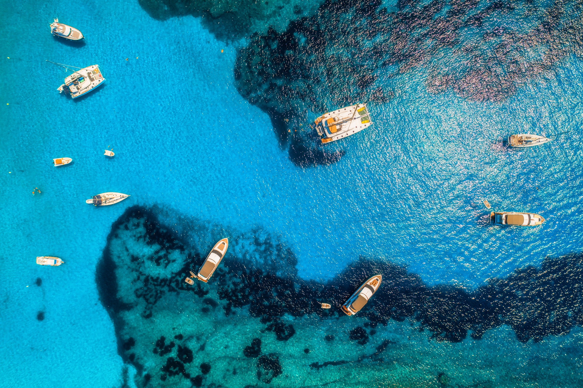 Aerial view of boats and luxury yachts in transparent blue sea